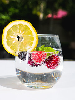 Wasser mit frischen Himbeeren garniert mit Zitrone